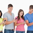 Four friends standing to the side slightly sending texts - Stockfoto