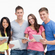 Stock Photo: Smiling group with tablet pc's in hand as they look at cam