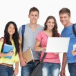 A smiling group of students holding a laptop while looking at th — Stock Photo #13959678