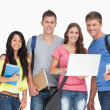 A smiling group of students holding a laptop while looking at th — Stock Photo