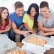 A laughing group of friends gathered around some pizza - Stock Photo