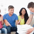 Friends celebrating as one guy brings pizza to them — Stock Photo
