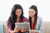 A woman with her friend smiling as they both look at the tablet — Stock Photo