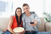 A couple embracing while on the couch changing the channel — Stock Photo