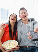 A laughing couple sitting on the couch with popcorn as they watc — Stock Photo