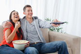 A laughing couple enjoying a tv show together as they hold each — Stock Photo