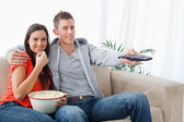 A couple eating popcorn and using the tv remote while looking at — Stock Photo