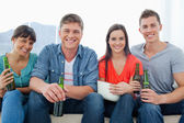A smiling group sitting on the couch while holding beers — Stock Photo