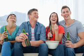 Laughing group of friends sitting with beers in their hands and — Stock Photo