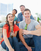 A laughing group sitting on the couch and the floor with beers i — Stock Photo