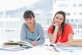 Two smiling students studying together while looking at the came — Stock Photo