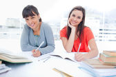 Two girls smiling and looking into the camera as they do homewor — Stock Photo