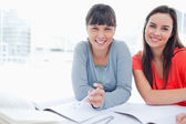 Two students sitting beside each other smiling as they work — Stock Photo