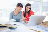 Two girls smiling as they use the laptop as one girl points at s — Stock Photo