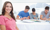 A smiling woman sits in front of her three friends who are study — Stockfoto