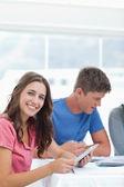 Een lachende meisje zit en gebruikt haar tablet-pc met vrienden in de buurt van haar — Stockfoto