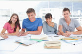 Four smiling students look up into the camera — Stock Photo