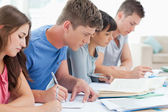 Vista lateral de cuatro estudiantes estudiar y escribir juntos — Foto de Stock
