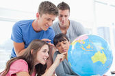 Students pointing to places in the world on a globe — Stock Photo