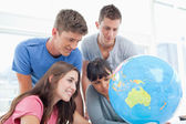 Four students look at the globe together — Stock Photo