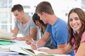 A side view of studying as one girl looks into the camera — Stock Photo