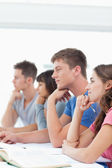 Four students listening in class while one looks tired — Stock Photo