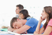 Four students in class as three pay attention one male student s — Stock Photo