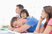 A sleeping student is being looked at by a confused fellow stude — Stock Photo