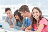 Three students look into the laptop as the fourth student looks — Stock Photo