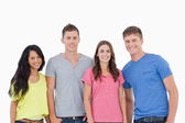 Four standing beside one another and smiling — Stock Photo