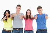 Four standing beside each other give thumbs up — 图库照片