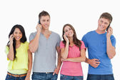 A smiling group of friends make calls while looking into the cam — Stock Photo