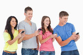 Four laughing friends sending texts on their phones — Stock Photo