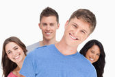 A man smiling with his head tilted and his friends behind him — Stock Photo
