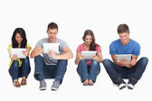 Four friends sitting on the ground all with tablets — Stock Photo