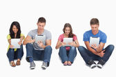 Four sitting beside each other using their tablets — Stock Photo