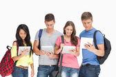 Estudantes com mochilas olhando seus comprimidos — Foto Stock