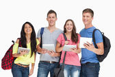 A group of students with tablets and backpacks smiling and looki — ストック写真