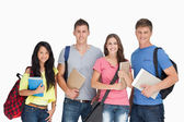 Students looking at the camera as they hold notepads — Stock Photo