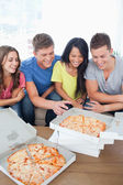 A laughing group of friends gathered around some pizza — Stock Photo