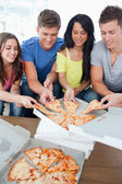 A group grabbing themselves a slice of the pizza — Stock Photo