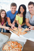 Smiling friends taking some pizza as they look at the camera — Stock Photo