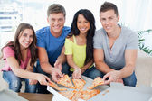 A group of friends taking a slice of pizza each as they look at — Stock Photo