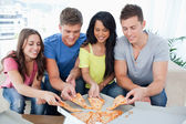 Friends grabbing some pizza as they look at the box — Stock Photo