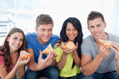 Friends about to eat their pizza as they look at the camera — Stock Photo