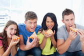 About to eat pizza as they look at the camera — Stock Photo