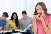 A woman in front of her friends as she is about to eat a slice o — Stock Photo