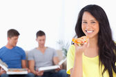Woman smiling and looking at the camera as she holds pizza — Stock Photo