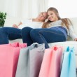 Smiling girls sitting on the couch with their bags of shopping — Stock Photo