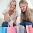 Girls looking into their shopping bags for a item to try on — Stock Photo